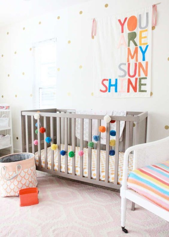 a colorful gender neutral nursery with grey and white furniture, colorful letters and garlands, printed textiles and a polka dot wall