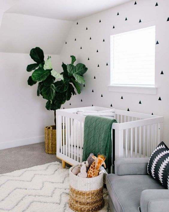 a contemporary gender neutral nursery with a geometric wall, neutral furniture, green and neutral textiles is welcoming