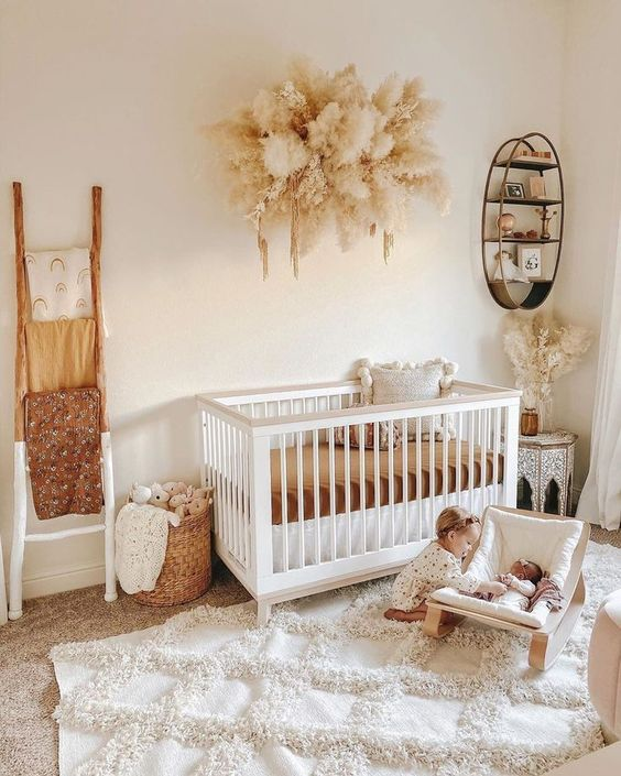 a gender neutral nursery done in warm neutrals, with white and neutral furniture, pampas grass, toys and layered rugs
