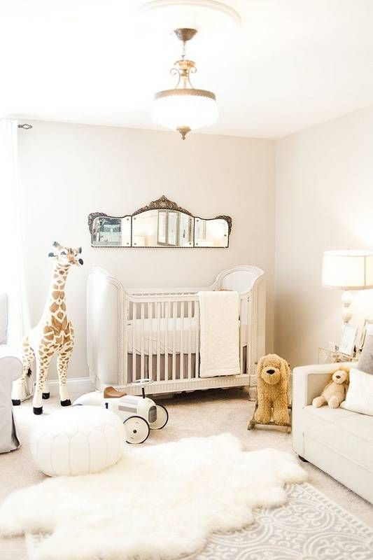 a neutral nursery with a refined crib, white furniture, a vintage mirror and layered rugs plus chic toys