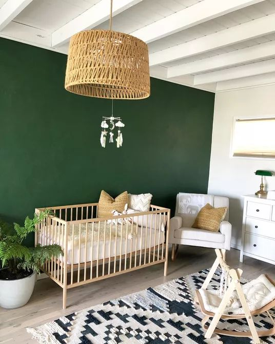 a mid-century modern boho nursery with a green accent wall, white and light-colored furniture, a printed rug and a woven lamp