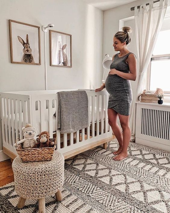 a gender neutral nursery with bunny artworks, a woven rug and ottoman on wooden legs is ultimate cuteness and chic