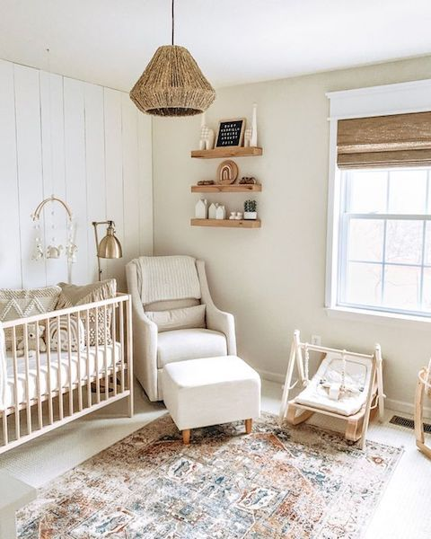 a farmhouse neutral nursery with light-colored furniture, a boho rug, a woven lamp and wooden furniture