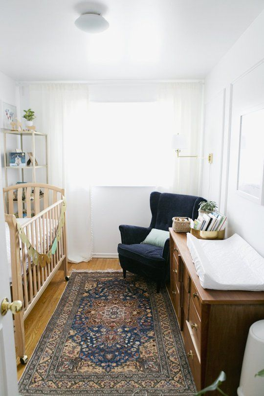 a gender neutral nursery with retro wooden furniture, a navy chair, a boho rug and shelves