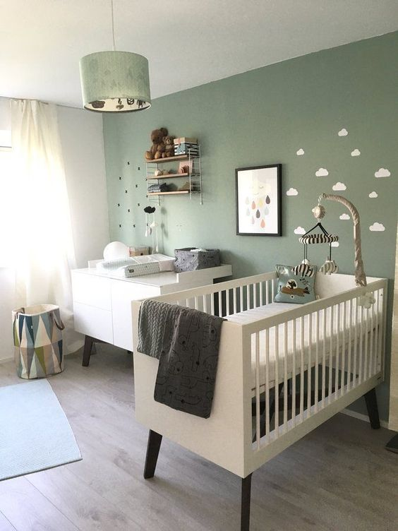 a gender neutral nursery with a green wall, minimal and sleek furniture, a green pendant lamp and some art and accessories