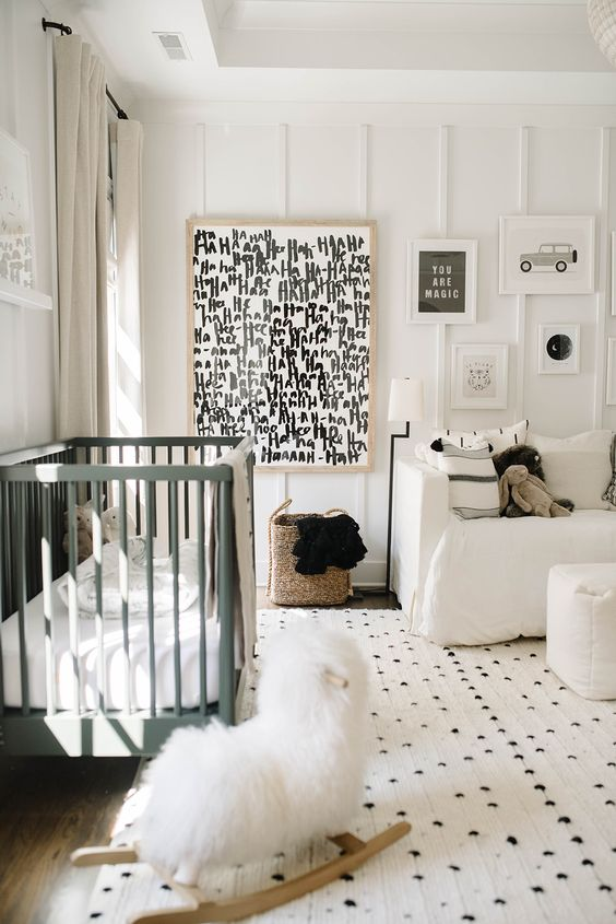 a monochromatic nursery with printed textiles and a graphic artwork, neutral and green furniture and paneling on the wall