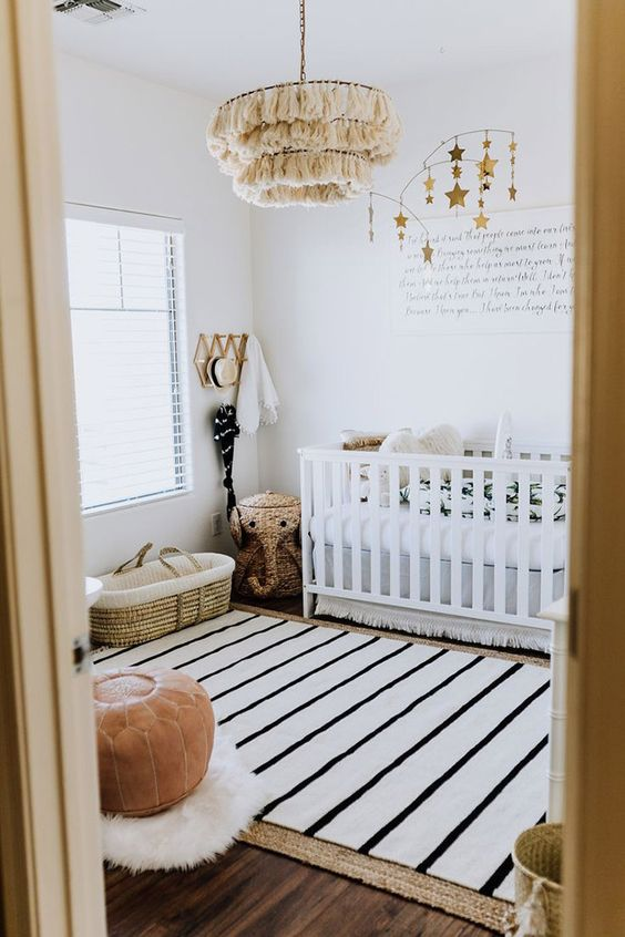 a gorgeous boho nursery with a white crib, a star mobile, a tassel chandelier, a leather ottoman and layered rugs