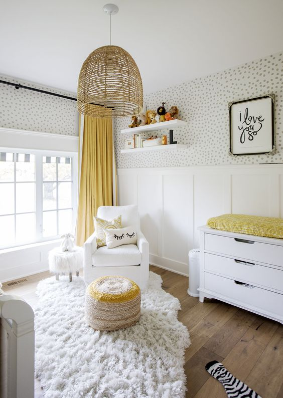 a pretty gender neutral nursery with a wallpaper and panel wall, white furniture, a woven lamp and touches of bright yellow