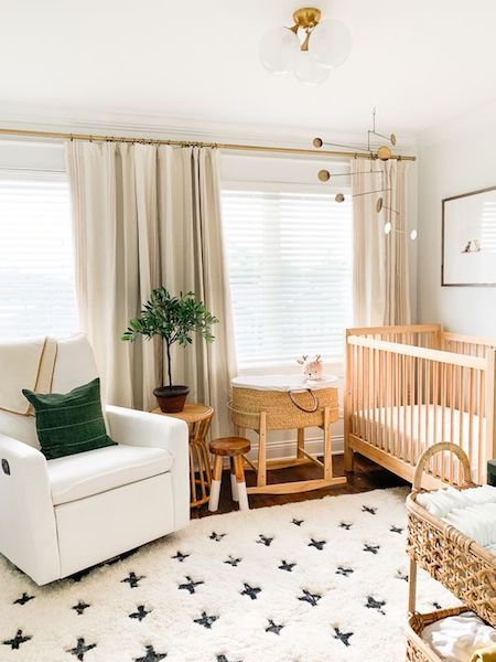 a welcoming gender neutral nursery with wooden and white furniture, a printed rug, baskets and a green pillow