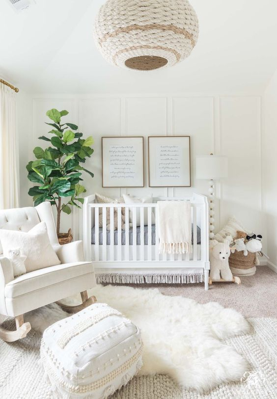 a welcoming white nursery with a wicker lampshade, a knit and fur rug, a white chair and baskets for storage