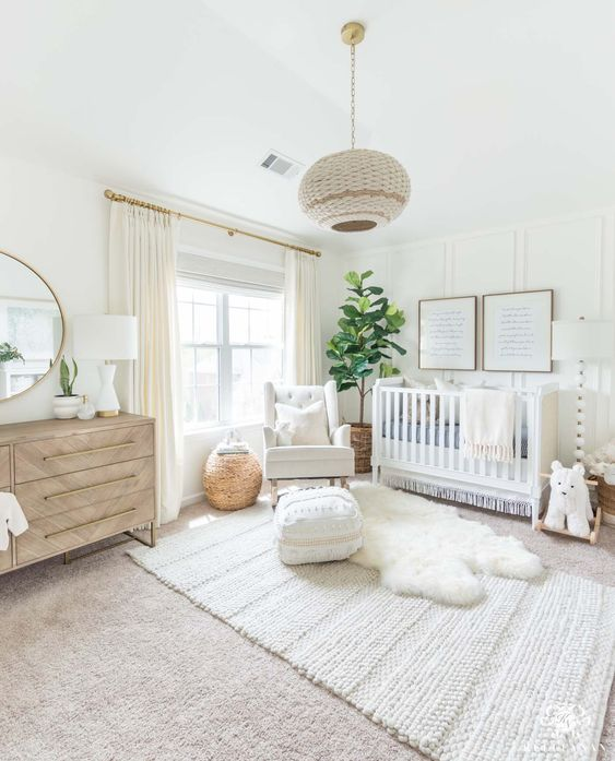 a soft and modern nursery with white walls and woodland decor and touches of boho is a gorgeous space