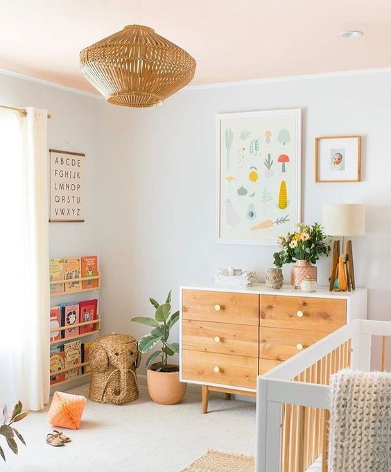 a neutral nursery with light stained furniture, a rattan lamp, colorful artworks and colorful books