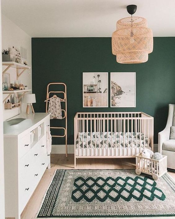 a stylish boho modern nursery with a hunter green accent wall, light-colored furniture, a woven chandelier and printed textiles
