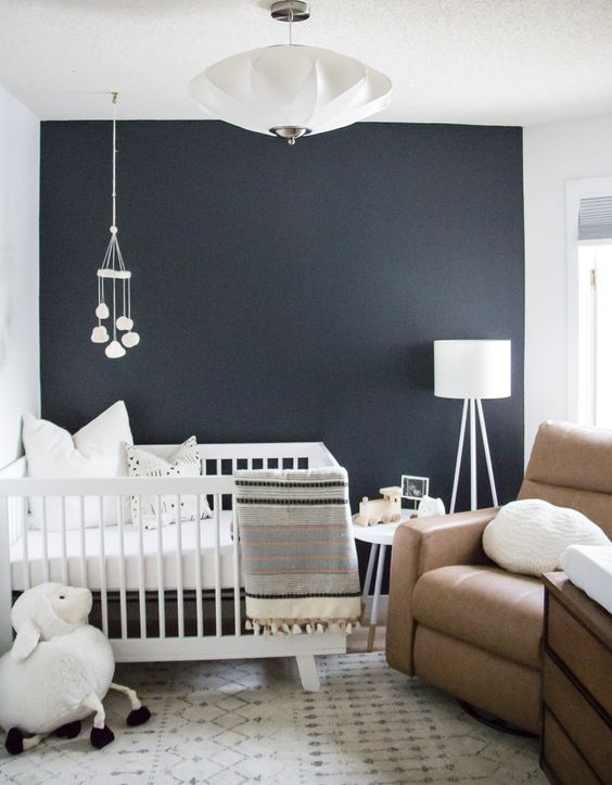 a small yet welcoming nursery with a navy accent wall, a brown leather chair and some white furniture