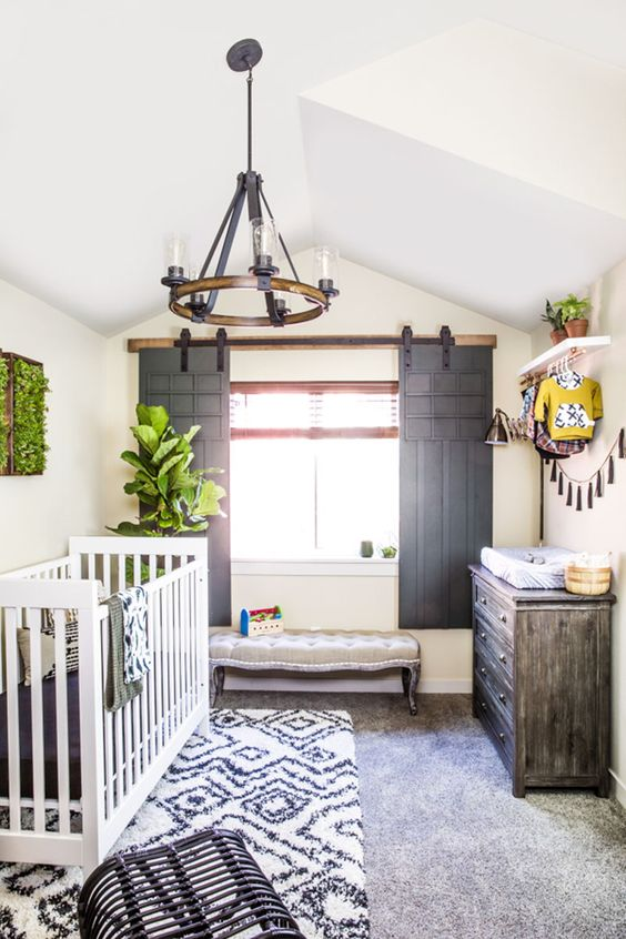 a rustic nursery with sliding shutters, a wooden chandelier, a weathered dresser and prints is a welcoming space