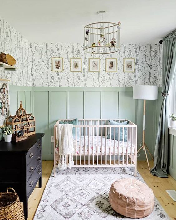 a welcoming modern nursery with green paneling, a black sideboard, a blush crib and a leather ottoman