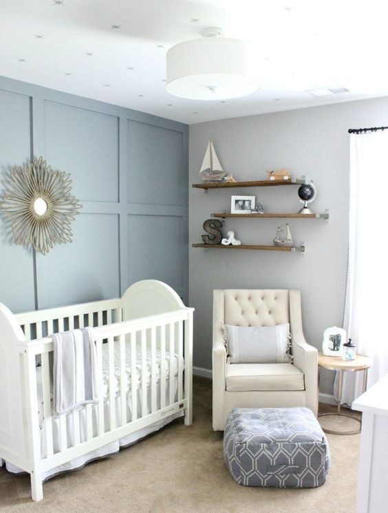 a slate blue and grey nursery with chic white furniture, open shelves and a ceiling lamp is very chic
