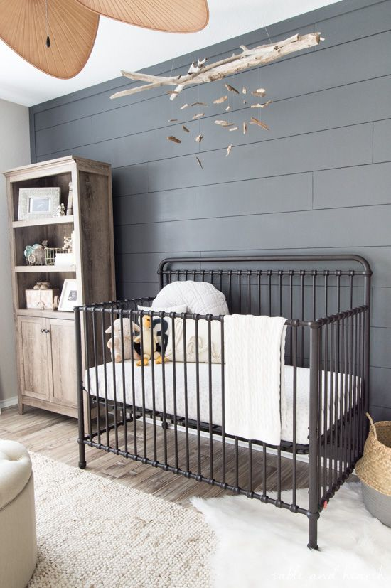 a rustic gender neutral nursery with a grey accent wall, a reclaimed wood storage unit and a black metal crib