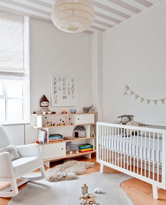 a mid-century modern gender neutral nursery with white and neutral furniture, with neutral textiles and colorful toys and books plus garlands