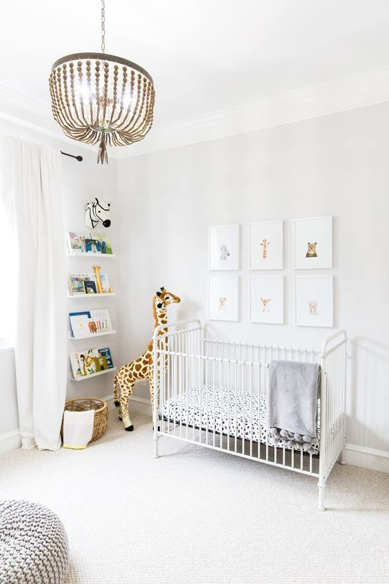 an airy contemporary nursery with a gallery wall, a white crib, a grey chunky knit ottoman and open shelves