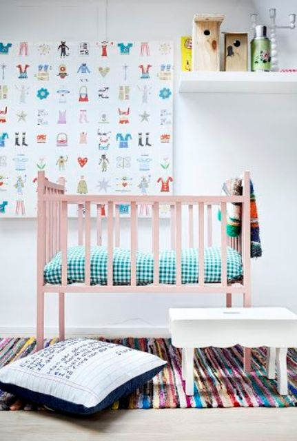 a gender neutral nursery with a pink bed, colorful bedding and textiles, a bold artwork and some accessories