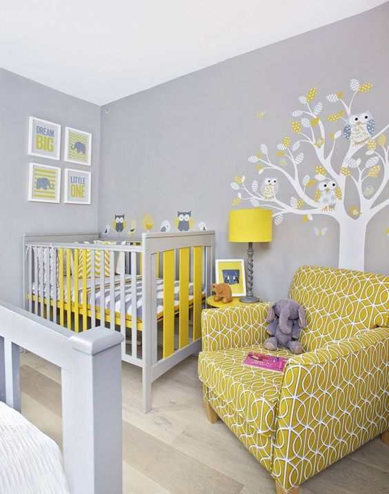 a grey nursery with bright mustard touches, a tree on the wall, a mustard printed chair and a mustard lamp is very bright and fun