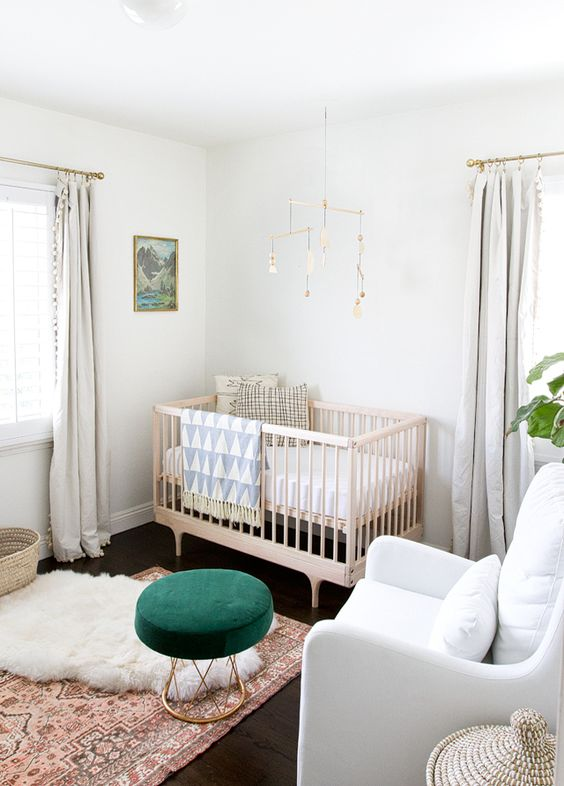 a gender neutral space with neutral textiles and upholstery, a wooden crib and a bright emerald ottoman and prints to enliven the space