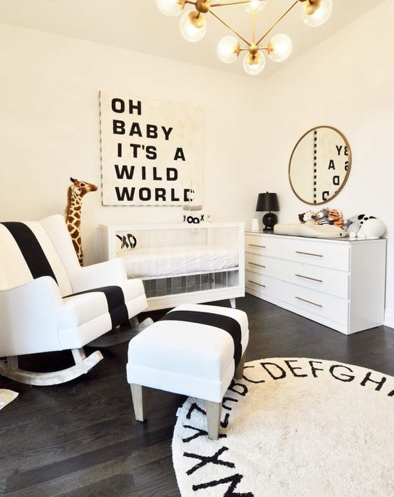 an elegant and refined monochromatic nursery with an acrylic crib, black and white art, a rug and a bold rocker