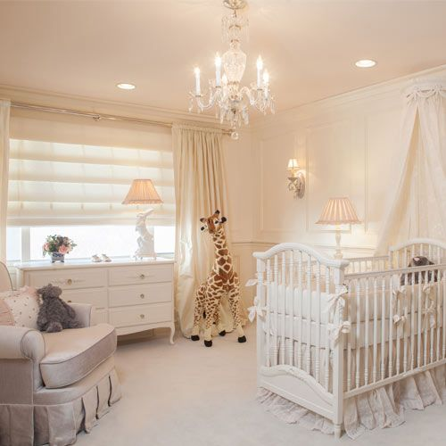 a gender-neutral and neutral nursery with vintage glam touches, a crib with ruffles, a glam vintage chandelier, curtains and shades and some pretty toys