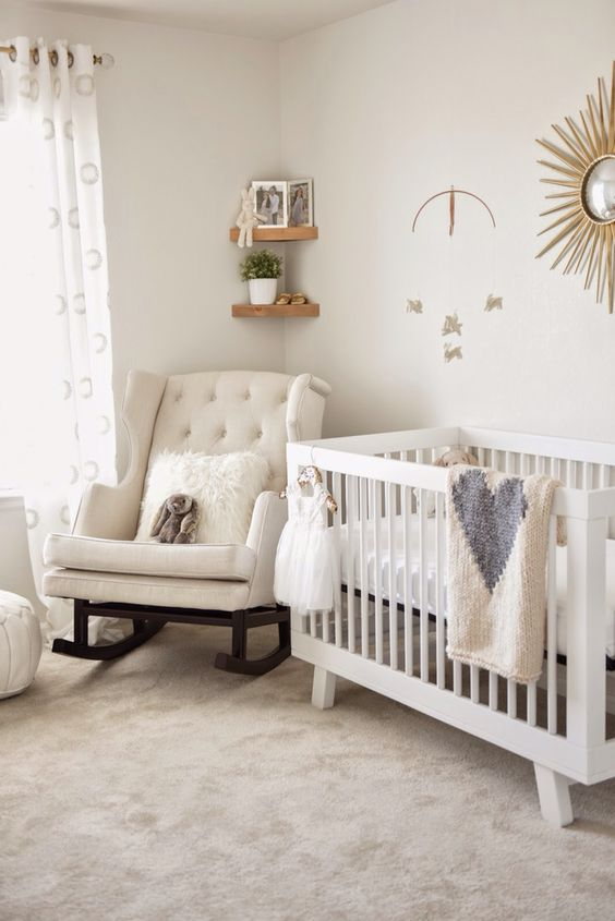 a neutral nursery with chic and cozy neutral furniture, triangle wooden shelves, a sunburst mirror and some simple bedding