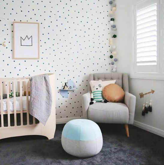 a gender neutral nursery with a spotted wall, a wooden crib, a grey chair and a blue ottoman and some plush and soft touches