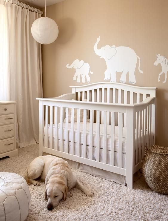 a gender neutral nursery with tan walls and elegant white furniture, faux fur and a pendant lamp is very welcoming
