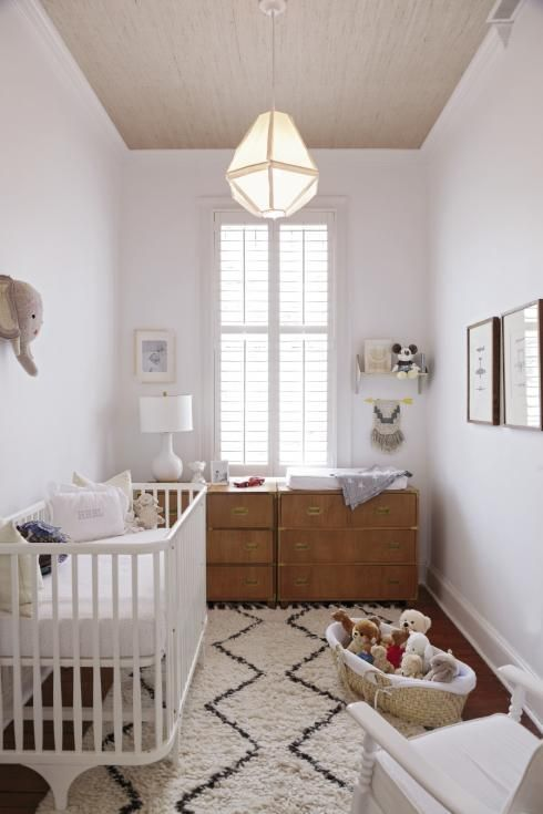 a neutral and peaceful nursery with white and light colored furniture, artworks and faux taxidermy plus lots of toys