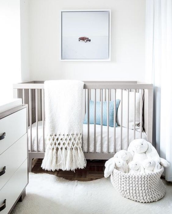 a white gender-neutral nursery with white and grey furniture, white and blue bedding, toys and an artwork is serene and airy