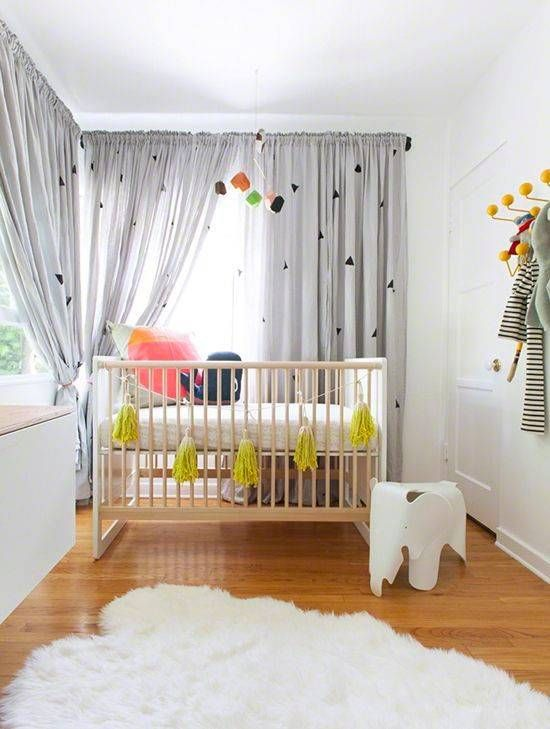 a stylish gender neutral nursery with simple and minimal furniture, grey curtains, colorful bedding and a bold mustard tassel garland