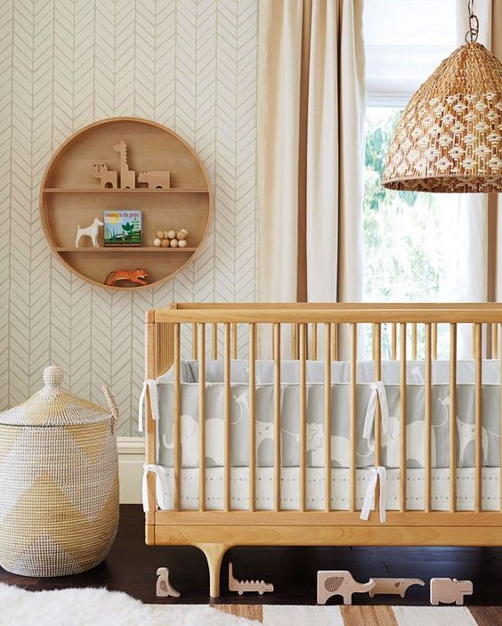 a gender neutral nursery with light-colored furniture, printed bedding, a basket and a round wooden shelf is a very chic space