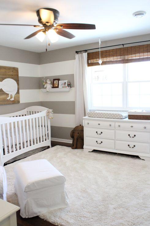 a neutral farmhouse nursery with a striped accent wall, white vintage furniture, a white faux fur rug, woven shades, neutral bedding