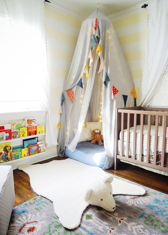 a colorful gender neutral nursery with a wooden crib, a teepee, colorful garlands and banners and bright books on the shelf