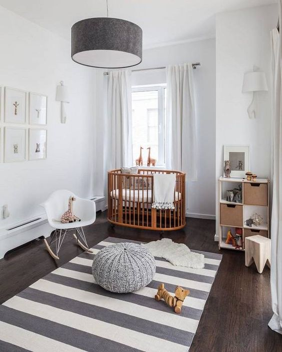 a stylish grey and white nursery with neutral furniture, a wooden crib, some simple textiles and a gallery wall is very welcoming