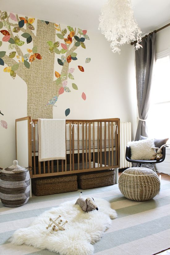 a gender neutral nursery with mid-century modern and boho furniture, a tree on the wall and cozy and simple textiles including faux fur