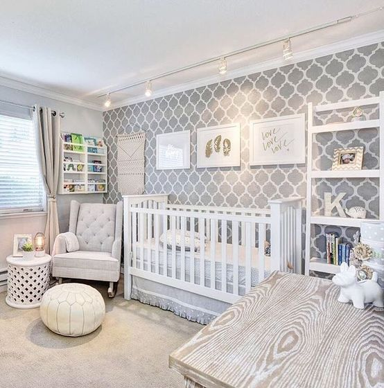 a gender neutral nursery with an accent wallpaper wall, white furniture, lights and white and neutral toys