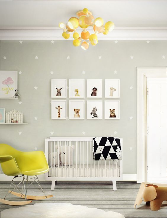 a gender neutral nursery in grey and white with bold yellow touches, with a printed wall, a gallery wall, a bold modern chandelier and a chair