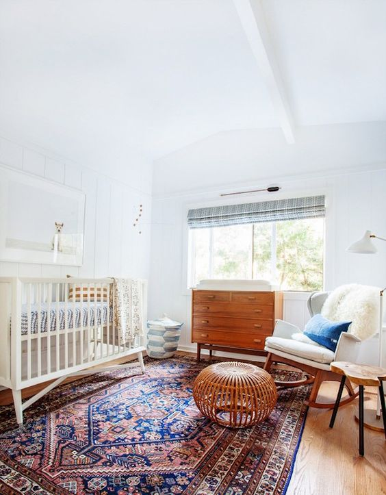 a serene and cozy mid-century modern nursery with stained and white furniture, a printed rug and faux fur is a stylish space