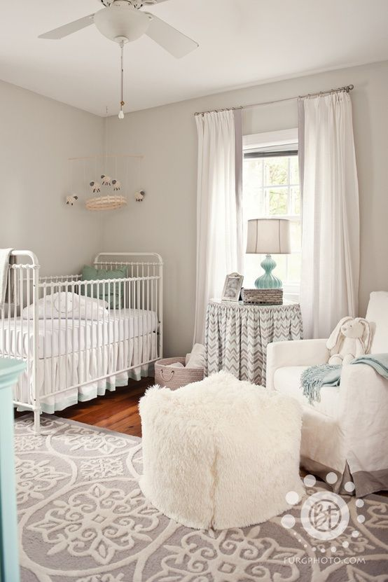a neutral farmhouse nursery with grey walls, vintage furniture, white and printed textiles and touches of mint blue