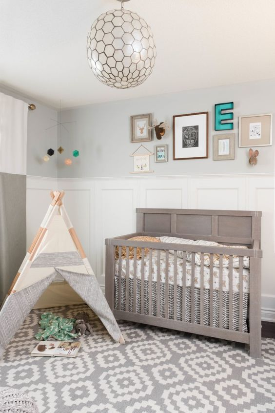 a neutral boho farmhouse nursery with paneling and grey walls, a grey crib and a teepee plus a chic gallery wall