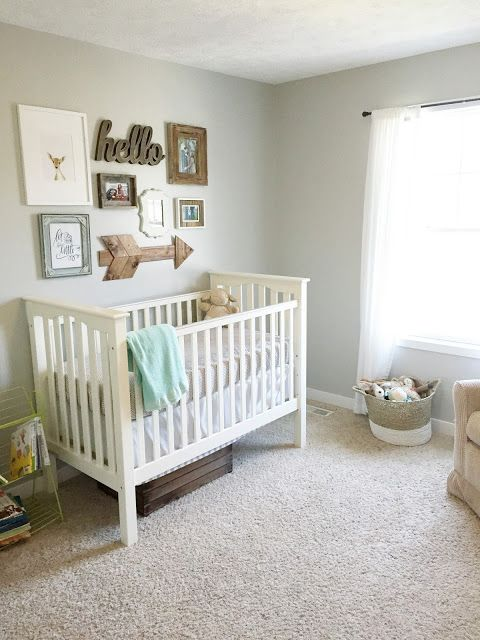 a neutral and welcoming nursery with grey walls, grey and white furniture, a gallery wall and some toys that match