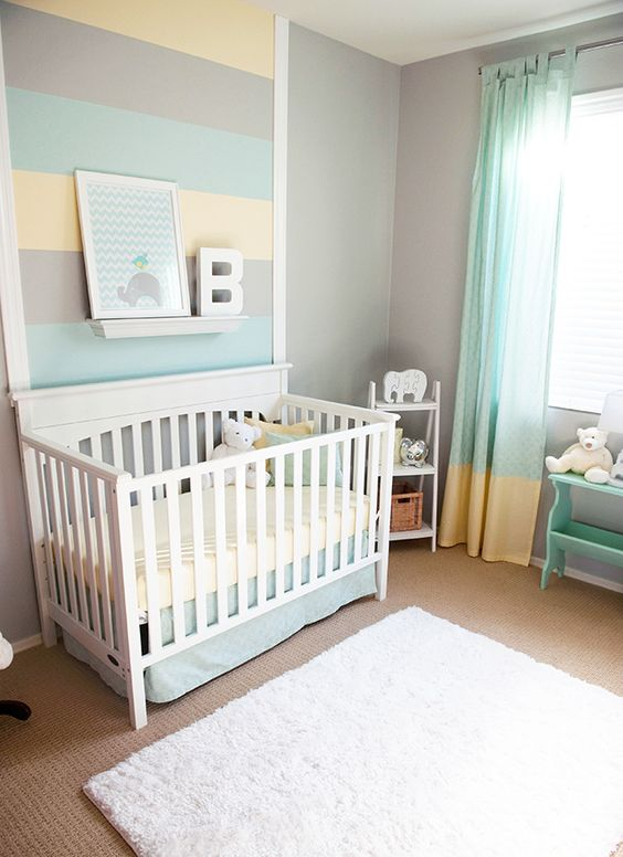 a colorful gender neutral nursery with striped walls and color block curtains, with white and mint furniture and some art