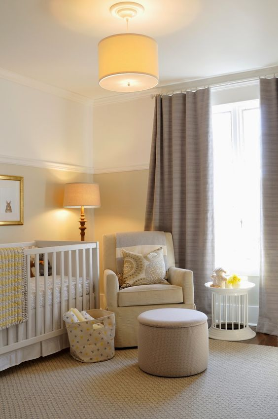a welcoming and cozy neutral nursery with color block walls, touches of tan, yellow and taupe curtains, lamps that match
