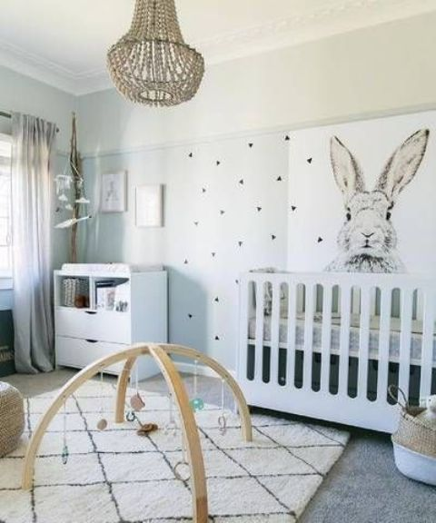 a gender neutral nursery with a printed wall, white modern furniture, a beaded chandelier and artworks and toys