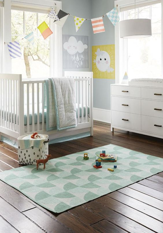 a gender neutral nursery with blue walls, chic white furniture, printed and colorful textiles and garlands, bright artworks